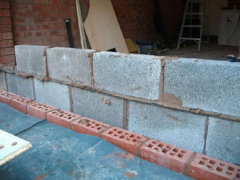 The double skin new wall has concrete blocks inside and a red brick exterior